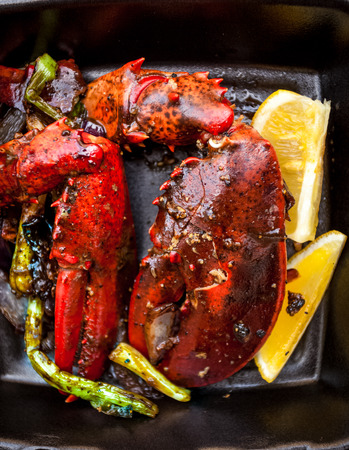 Closeup photo of cooked lobster claw with lemon and vegetables