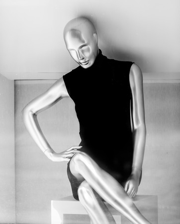 Black and white photo of female mannequin in dress photo