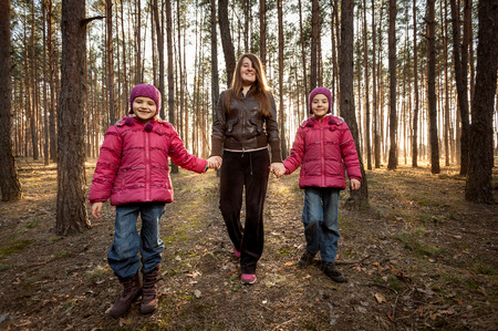 beautiful mother and two daughters walking at sunny forest photo