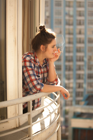 unhealthy thoughts: Toned photo of hipster girl smoking out of widow Stock Photo