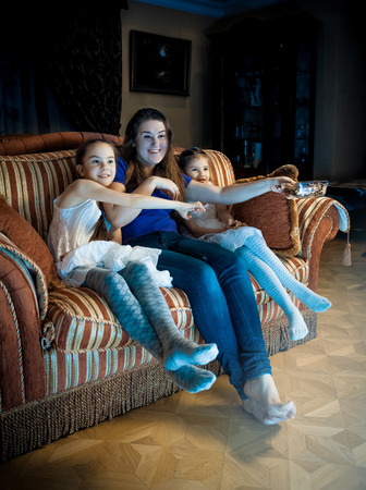 Photo of family with kids watching TV at late evening Stockfoto