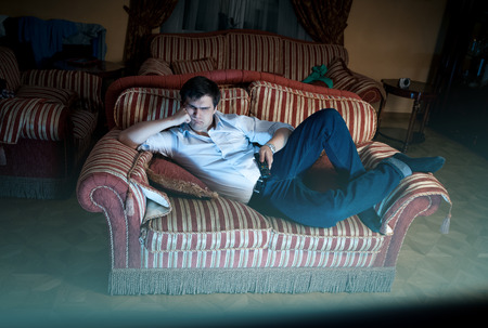 若い男はソファに横になっていると、夜にテレビを見ています。