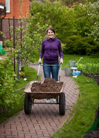 Beautiful smiling woman carrying garden wheelbarrow photo