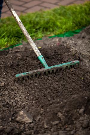 Closeup photo of rake on garden bed