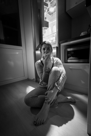 Black and white photo of woman sitting next to fridge at night photo