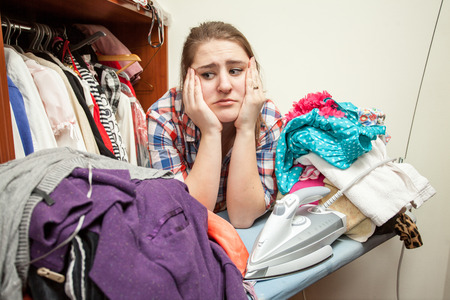 ironed: Young sad woman leaning against huge pile of not ironed clothes Stock Photo