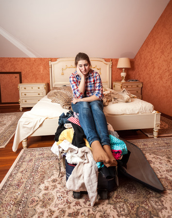 unpacked: Portrait of depressed woman sitting on unpacked suitcase at bedroom Stock Photo