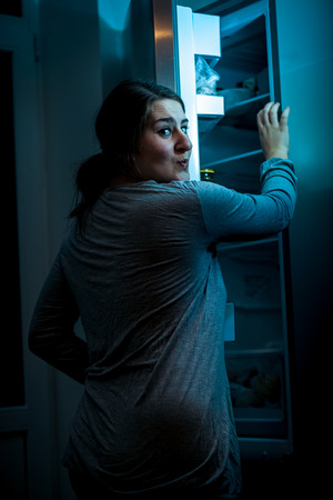 sleepwalker: Photo at night of woman opening refrigerator Stock Photo