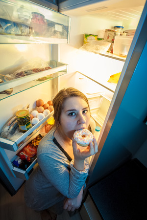 Portrait of young woman in pajamas eating donut next to refrigerator