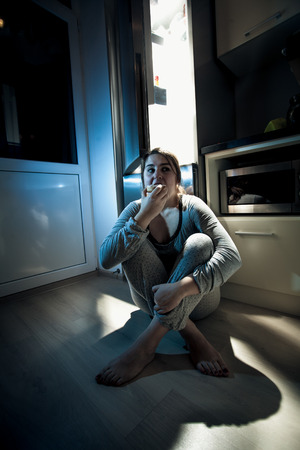 Woman eating donut on kitchen at night photo