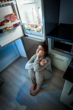 Hungry woman sitting on floor and looking at fridge at night photo