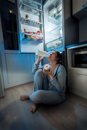 Portrait of young woman sitting on floor at kitchen and having late dinner
