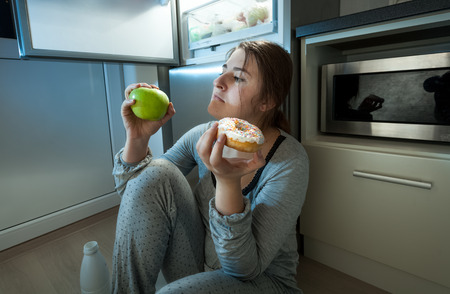 Closeup portrait of woman choosing between apple and donut at evening lunch
