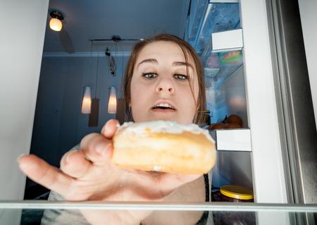 Wide angle portrait of woman taking donut from fridge Standard-Bild