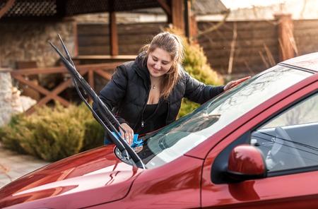 Portrait of beautiful woman washing car windscreen photo