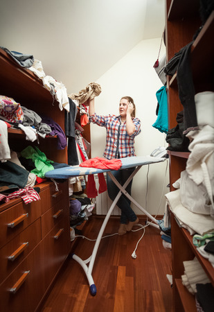 Young housewife looking at not ironed clothes at wardrobe photo