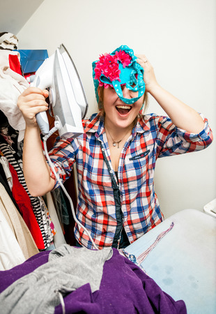 houseclean: Portrait of woman having fun with iron during housework Stock Photo