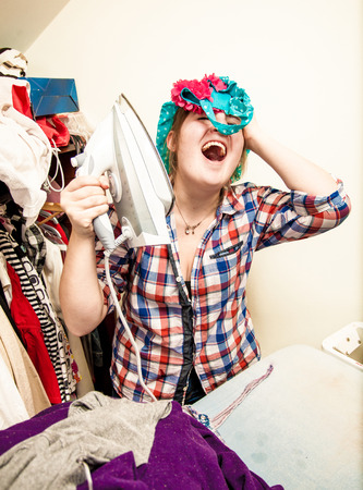 houseclean: Young woman singing and having fun during ironing