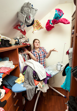 Portrait of smiling housewife in dressing room with clothes flying around photo