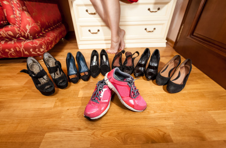 Slim female hand picking sneakers at wardrobe