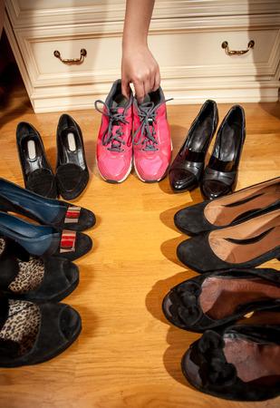 hugh: Closeup photo of woman choosing sneakers rather than hugh heeled shoes Stock Photo
