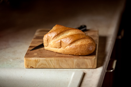 artisanal: Closeup photo of bread and knife on wooden desk