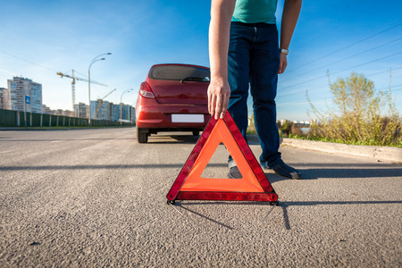 Young man placing red triangle sing on road after car crash photo