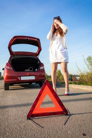 Depressed woman calling phone near crashed car photo