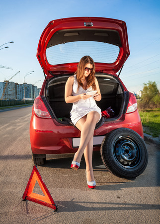 Sexy woman in short dress browsing on tablet how to change wheel photo