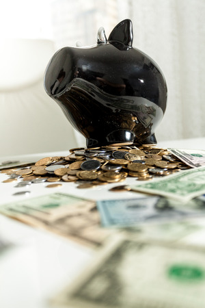 Photo of black piggy bank standing on pile of money photo