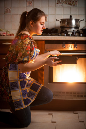 Closeup photo of housewife cooking cookies in oven photo