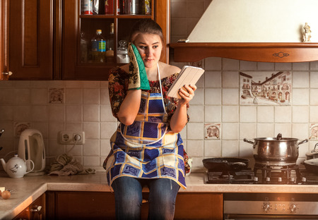 Portrait of amazed housewife looking recipe on tablet while sitting on tabletop photo
