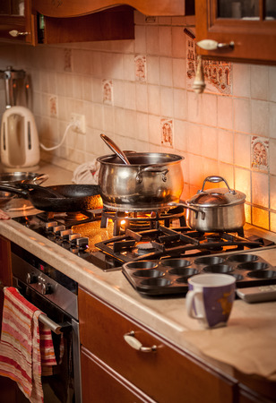 Closeup photo of metal pan boiling on burning gas stove on country style kitchen photo