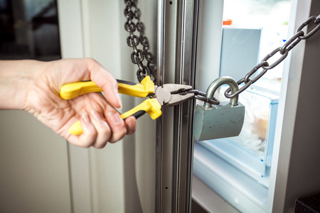 Closeup photo of woman cutting chain on fridge with pliers photo
