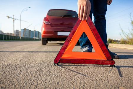 accidente laboral: Foto de detalle de hombre poniendo tri�ngulo se�al de advertencia en carretera Foto de archivo