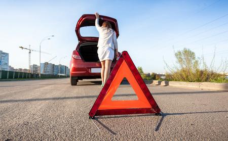 Photo of woman looking in trunk of broken car photo