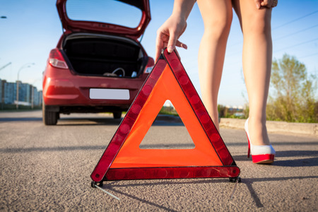Closeup photo of sexy woman putting warning sign on road photo