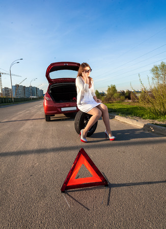 Sexy woman sitting on spare wheel against of broken car and warning sign photo