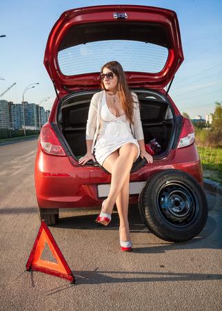 Sexy woman in short dress waiting for help near broken car photo