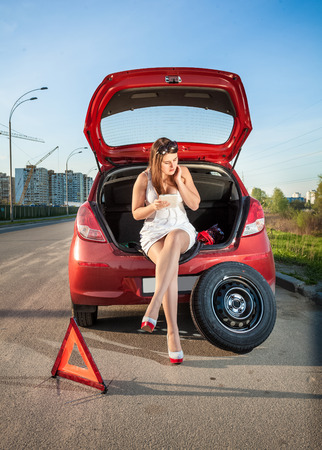 Sexy woman leaning against broken car and browsing hot to repair it on tablet photo