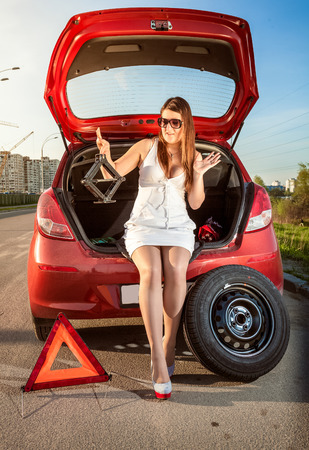 Beautiful woman looking on jack screw near car with punctured wheel photo