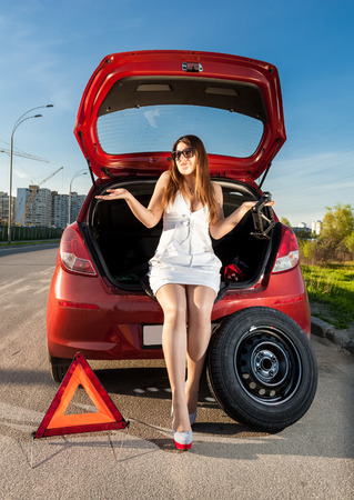 Sexy brunette woman sitting in trunk of broken car photo