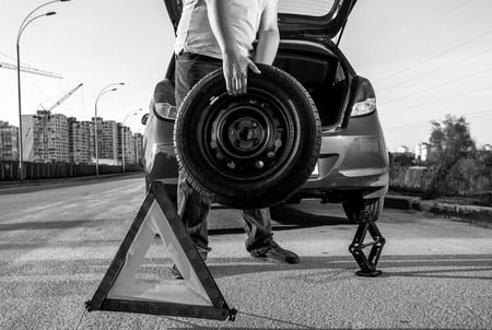 screw jack: Black and white closeup photo of man carrying spare wheel against broken car Stock Photo