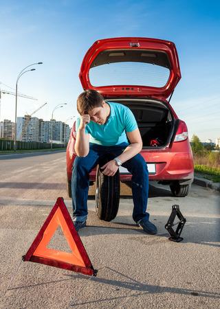Depressed man sitting on spare wheel near broken car photo