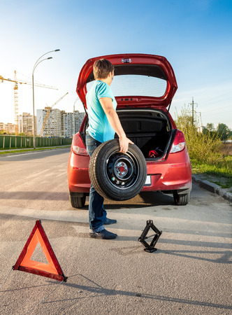 Photo of man taking spare wheel out of trunk photo