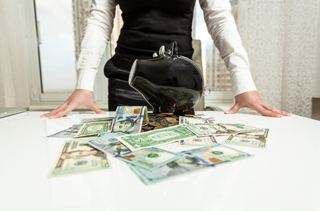 Business lady behind table with piggy bank and money photo
