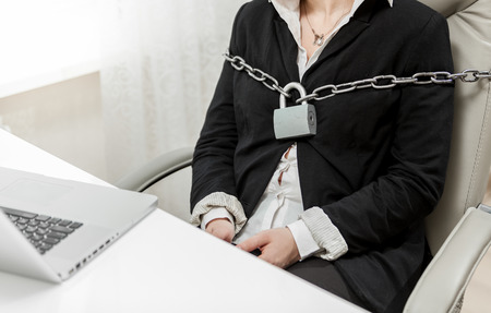 Closeup photo of businesswoman tied to chair by metal chain photo