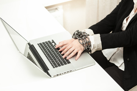 Photo of chained businesswoman typing on keyboard photo