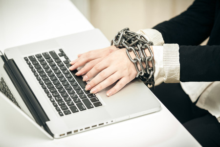 hard bound: Closeup photo of female hand chained up to laptop Stock Photo