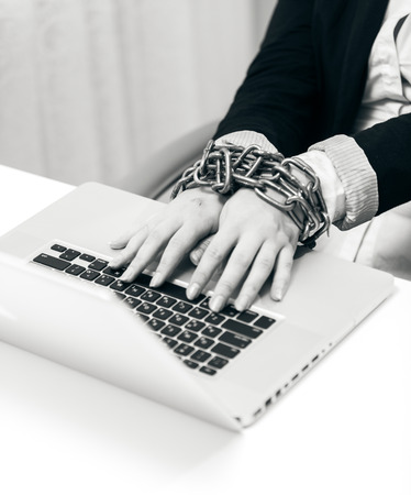 hard bound: Black and white closeup photo of woman locked to laptop by chain